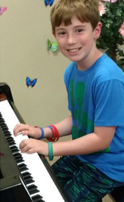 boy in blue shirt playing piano