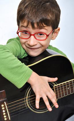 boy with green shirt playing guitar