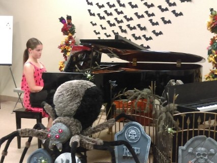girl at piano with spider and bat decor